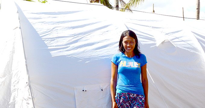 Rose Castro stands in front of the family tent which she received from Irish Aid after her home was destroyed by Typhoon Haiyan.